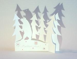Carte de vœux en papier découpé motif Ours et sapins, vue pliée de face avec texte manuscrit
