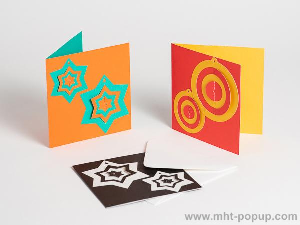 Carte de vœux en papier découpé bicolore, motifs boules et étoiles, 3 versions vert-orange, jaune or-rouge et noir-blanc de face, avec enveloppe