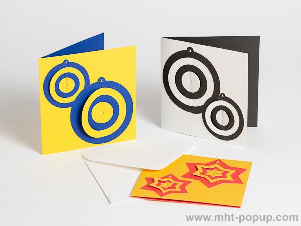Carte de vœux en papier découpé bicolore, motifs boules et étoiles, 3 versions bleu-jaune, noir-blanc et jaune or-rouge de face, avec enveloppe