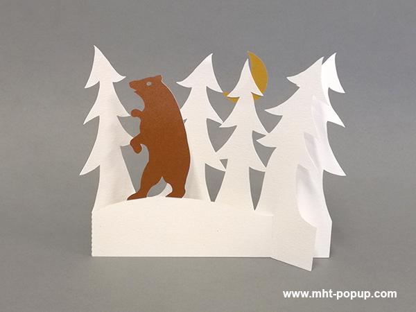 Décoration de Noël en papier découpé avec forêt de sapins et ours. Papier blanc, or, argent et cuivre. Pliage pour créer une scène en volume