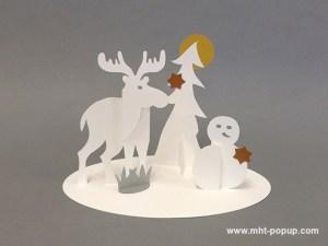 Saynète animalière d'hiver en papier découpé, modèle élan, bonhomme de neige. Papier blanc, or, argent et cuivre.