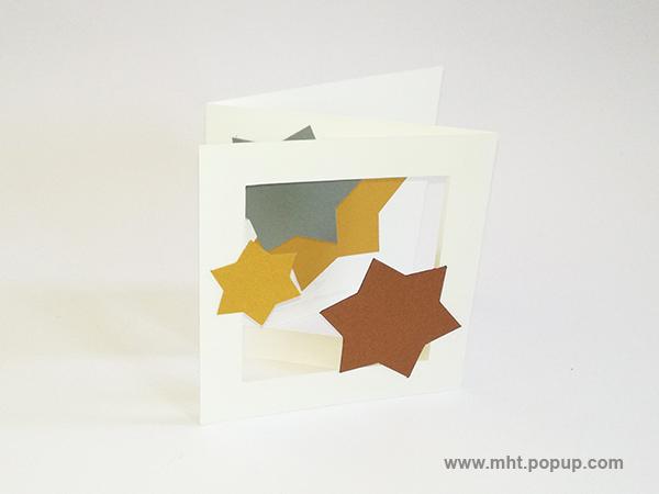 Cartes pop-up forme triptyque avec pliage en accordéon, motifs étoiles en papier or, argent et cuivre, vue de profil dessus droit avec pliage