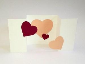 Carte à volets en accordéon, motifs cœurs en camaïeu rose et rouge, vue de face dépliée