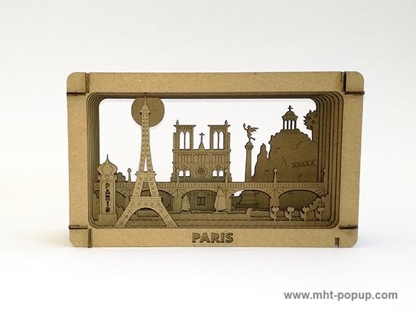 Diorama en carton brut avec éléments du patrimoine de Paris (Tour Eiffel, Notre Dame, Tuileries, Bastille, Buttes Chaumont, Seine, colonne Morris). Carton alvéolé recouvert de papier couleur. Gravure et découpe laser. Diorama à monter soi-même. Vue de face