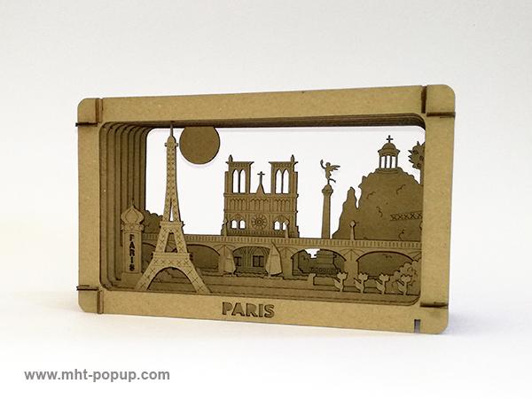 Diorama en carton brut avec éléments du patrimoine de Paris (Tour Eiffel, Notre Dame, Tuileries, Bastille, Buttes Chaumont, Seine, colonne Morris). Carton alvéolé recouvert de papier couleur. Gravure et découpe laser. Diorama à monter soi-même. Vue de profil gauche