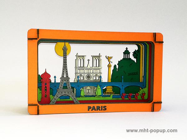 Diorama en couleur avec éléments du patrimoine de Paris (Tour Eiffel, Notre Dame, Tuileries, Bastille, Buttes Chaumont, Seine, colonne Morris). Carton alvéolé recouvert de papier couleur. Gravure et découpe laser. Diorama à monter soi-même. Vue de profil droit