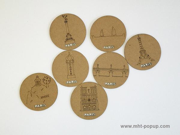 Magnets en carton brut avec motifs gravés du patrimoine de Paris (Tour Eiffel, Notre Dame, Tuileries, Bastille, Buttes Chaumont, Seine, colonne Morris). Vue d'ensemble