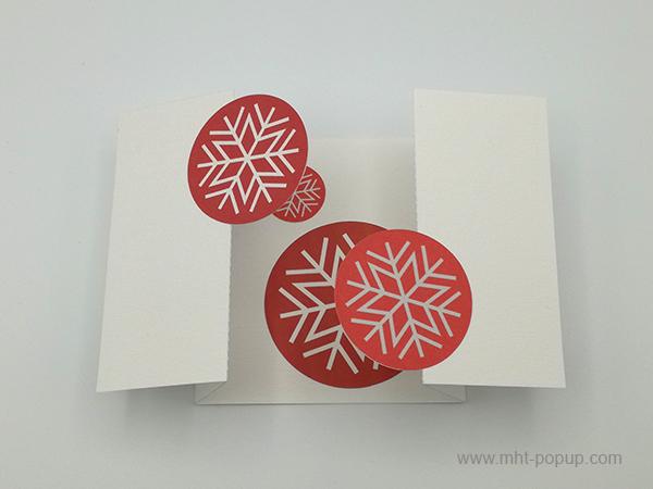 Carte de vœux à volets, motifs flocons rouges, vue de dessus carte ouverte