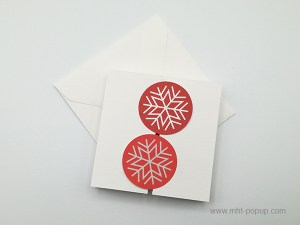 Carte de vœux à volets, motifs flocons rouges, vue de dessus carte fermée avec enveloppe