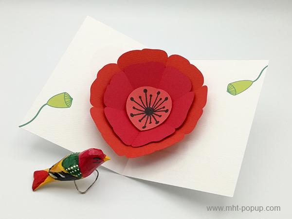 Carte pop-up Coquelicot rouge, vue de dessus de la carte ouverte mise en scène avec oiseau en bois