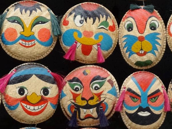 Différents exemples de masques peints sur des paniers retournés