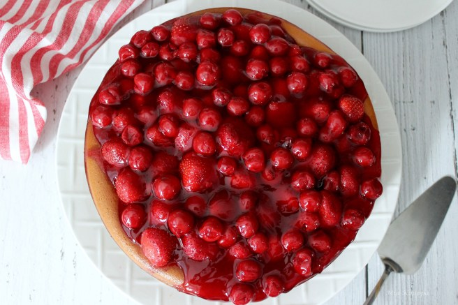 Cheesecake topped with strawberries and cherries