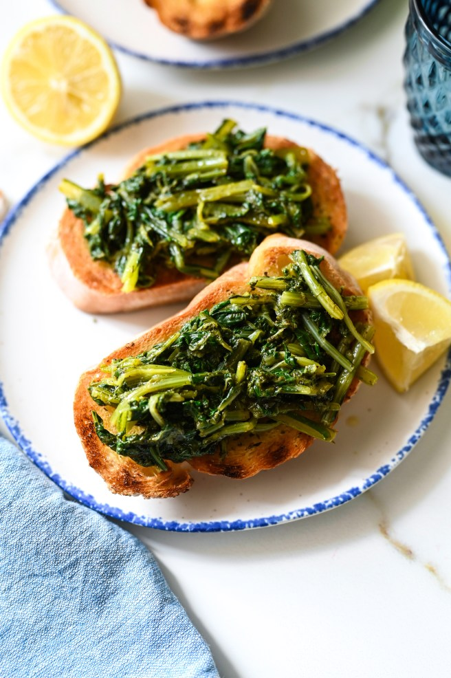 An open-face sandwich of dandelion greens and grilled bread flavoured with lemon, olive oil, garlic, oregano and feta