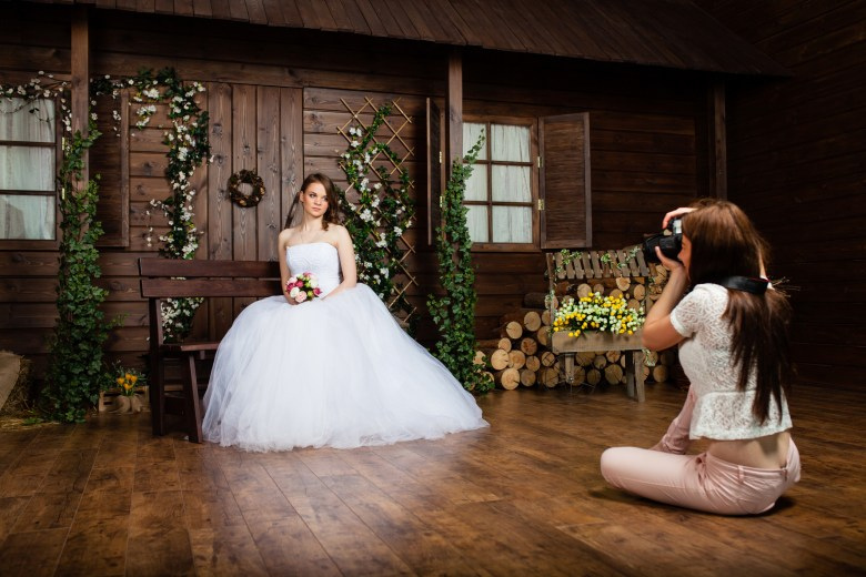 Photographer is taking pictures the bride in the studio