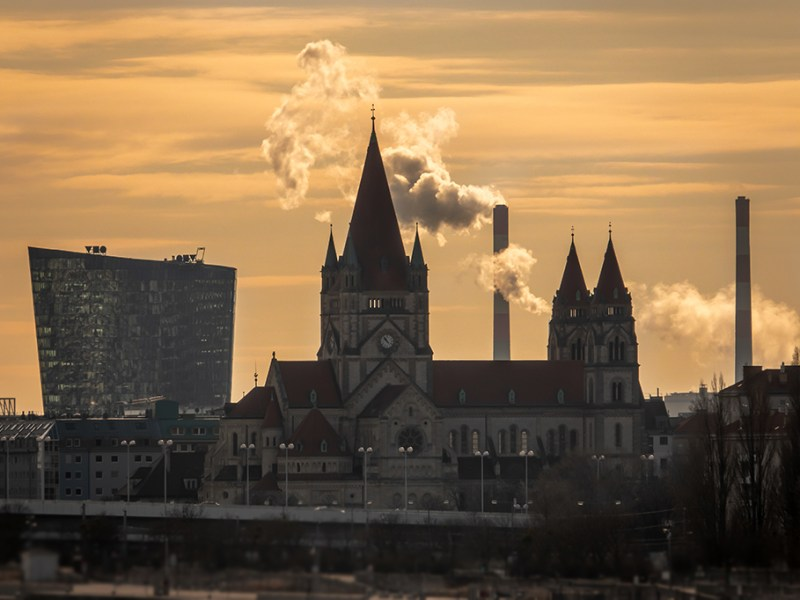 Gemischte Architektur, Franz von Assisi Kirche, davor die Reichsbrücke, im Hintergrund links das OMV Zentralgebäude, rechts die Schornsteine des Kraftwerkes Simmering, Wien, aufgenommen von der Brigittenauer Brücke