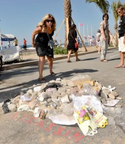 A-passer-by-spits-on-a-pile-of-rubbish-dedicated-to-the-Nice-terror-killer