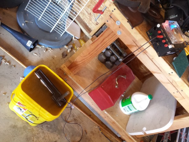 Here's my early electrolysis tank setup, using an old power supply unit from a computer and a kitty litter bucket filled with a baking soda electrolyte solution.