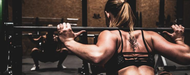 A woman performing back squats for Brehm