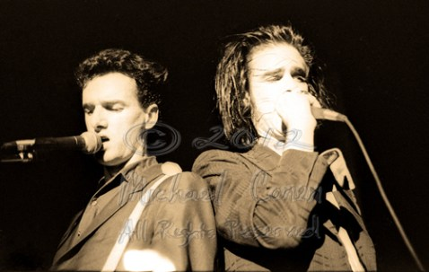 Mick Harvey plays and sings while Nick Cave's face is obscured by his hand on the mic