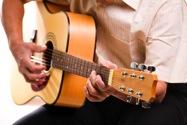 Mann spielt auf einer Akustikgitarre