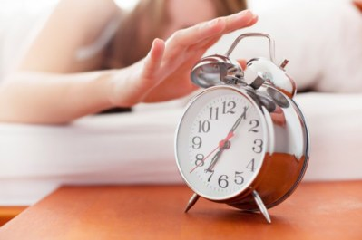 woman hitting snooze on alarm in the morning