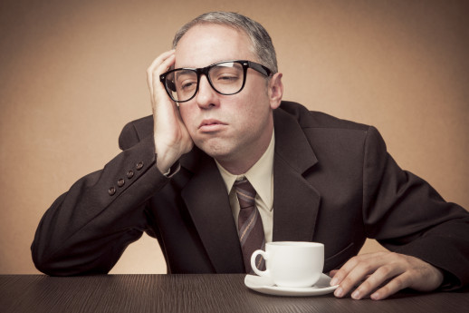 Nerdy businessman having problems staying awake, in need for coffee