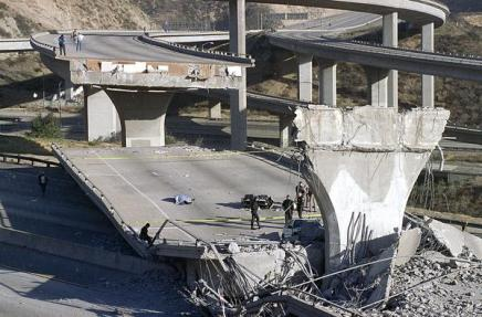 This January 17, 1994 photo shows the covered body of Los Angeles Police Officer Clarence Wayne Dean, 46, near his motorcycle which plunged off the State Highway 14 overpass that collapsed onto Interstate 5, an interchange that is now named in his memory. Dean was reporting to work in the predawn darkness and apparently never saw the collapsed bridge. # AP Photo/Doug Pizac