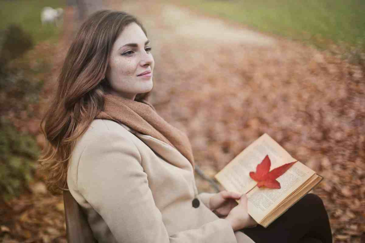 young woman with book in autumn park