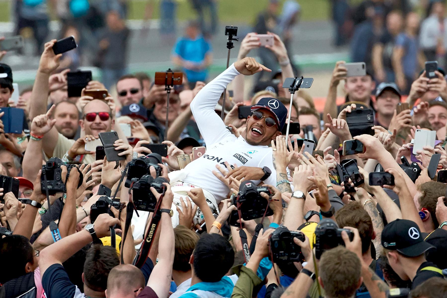 Lewis Hamilton surfs the crowd afeer winning the 2017 British Grand Prix.