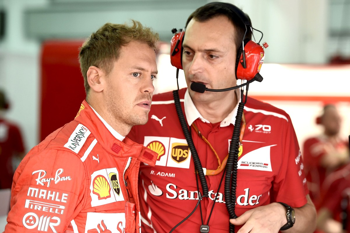 Sebastian Vettel talks with an engineer at the 2017 Malaysian Grand Prix.
