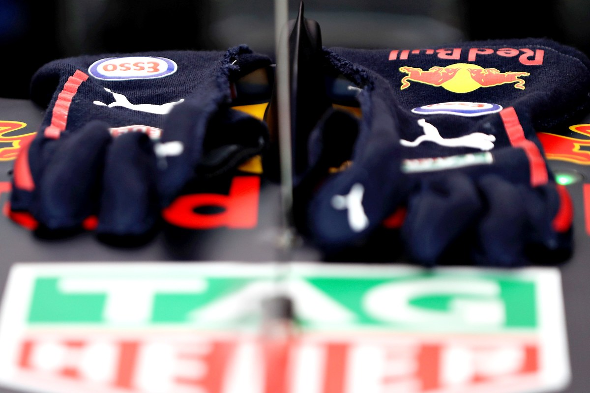 Max Verstappen's 2017 racing gloves rest on his car in its garage.
