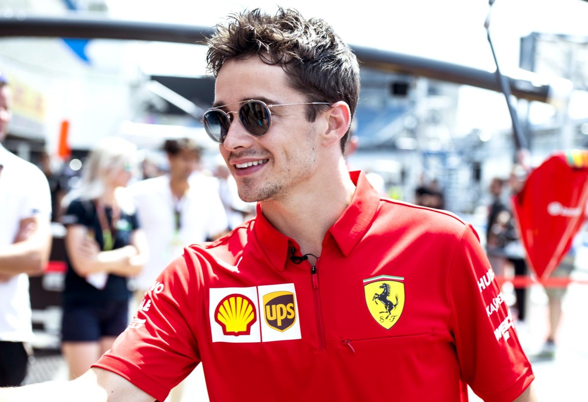 Charles Leclerc smiles in the pit lane at the 2019 German Grand Prix.