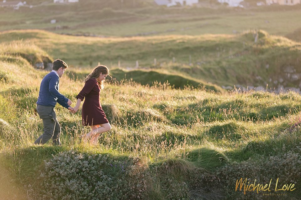 Engaged couple walking through a field