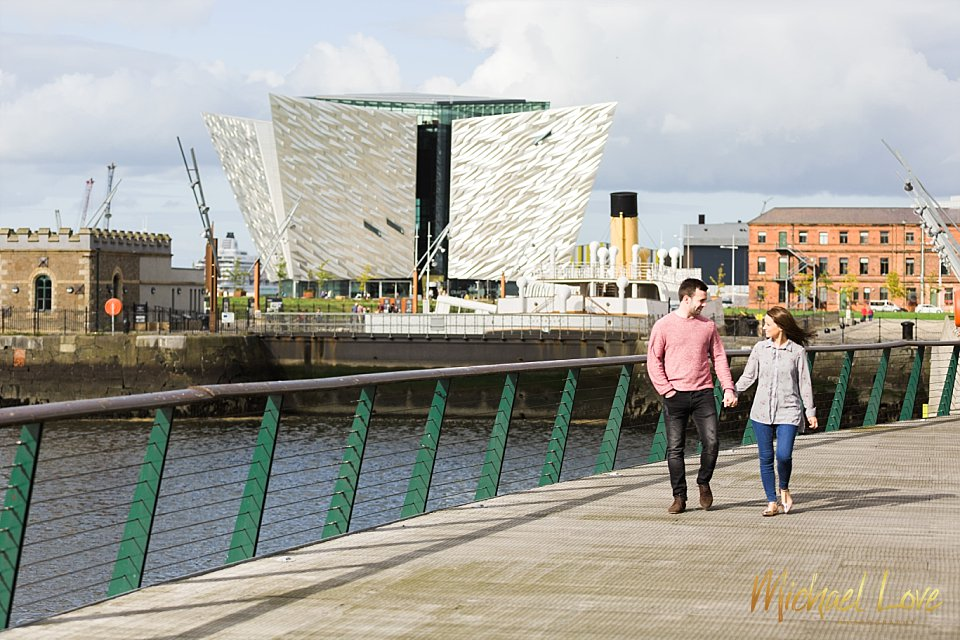 Engaged couple walking in front of the Titanic building in Belfast