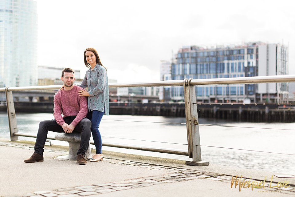 An engaged couple posing beside the river Lagan in Belfast