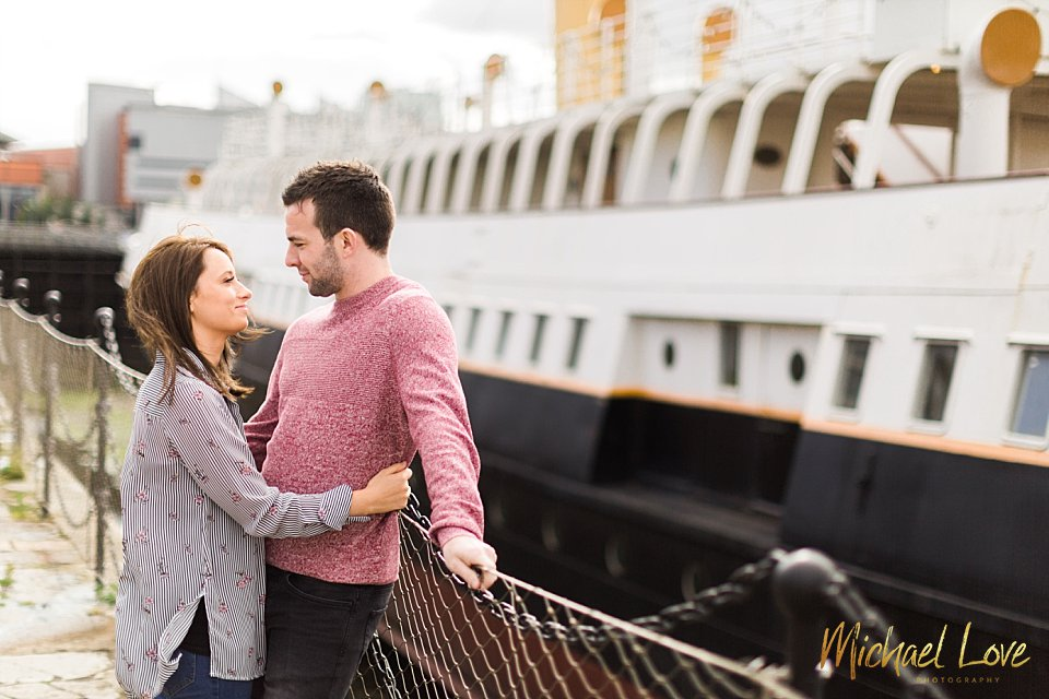 Engaged couple hugging front of old boat in Belfast