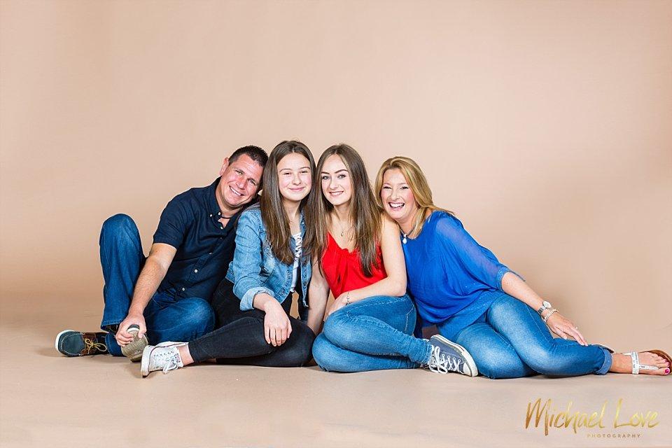 Family of four sitting on studio floor