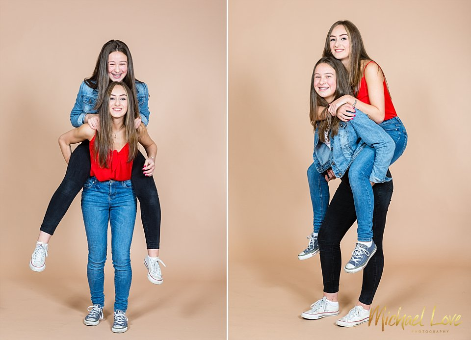 Two sisters giving piggyback in photo studio in Derry