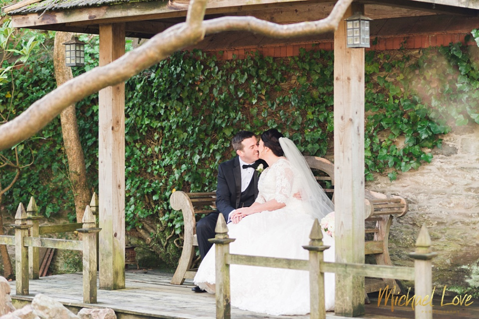 Bride & groom kissing in a garden gazebo