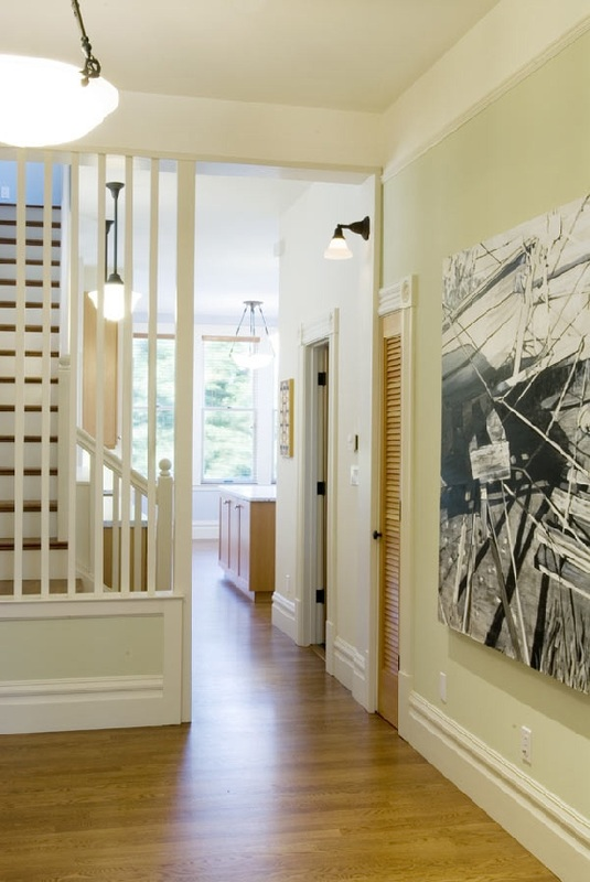 elegant fixture and wood floors lead through the hallway