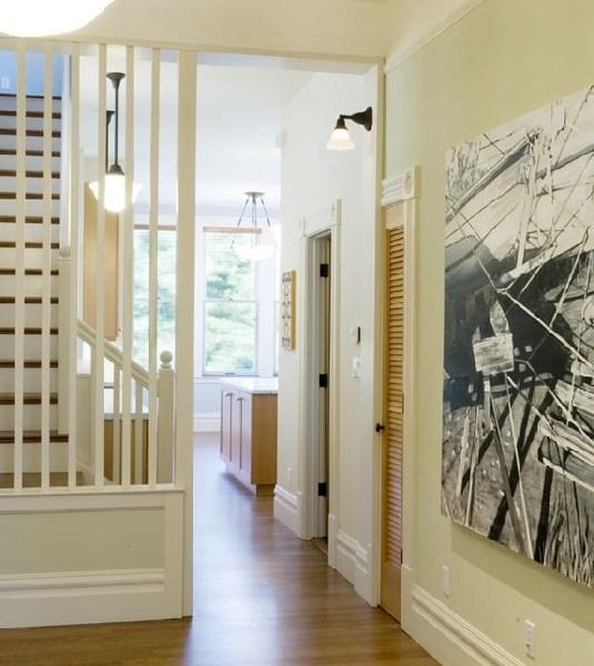 elegant fixture and wood floors lead through the hallway
