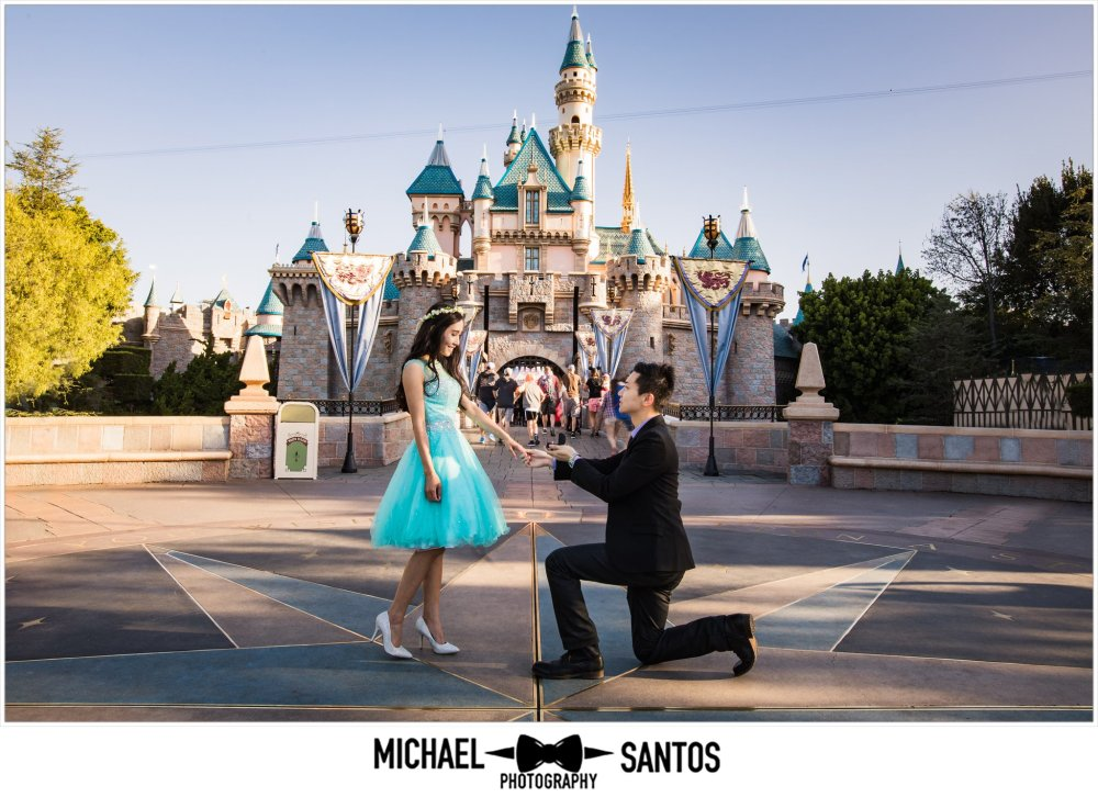 Couple proposing in front of castle at disneyland