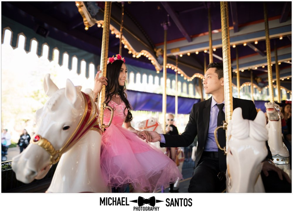 couple on carousel during engagement session at disneyland
