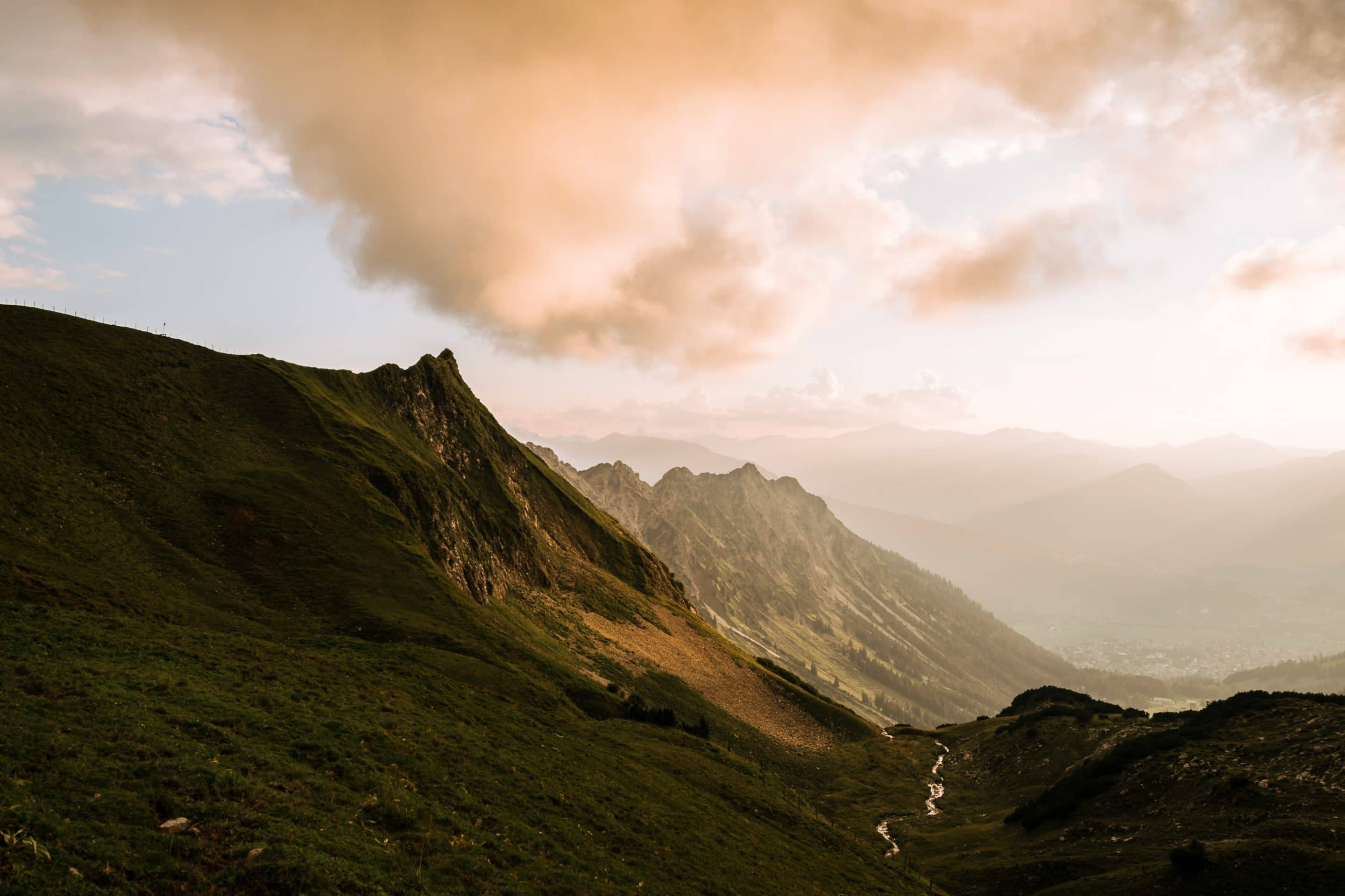 A beautiful burning sunset over the landscape of the Allgau Alps in southern Bavaria painting the mountain ridges orange by photographer Michael Schauer