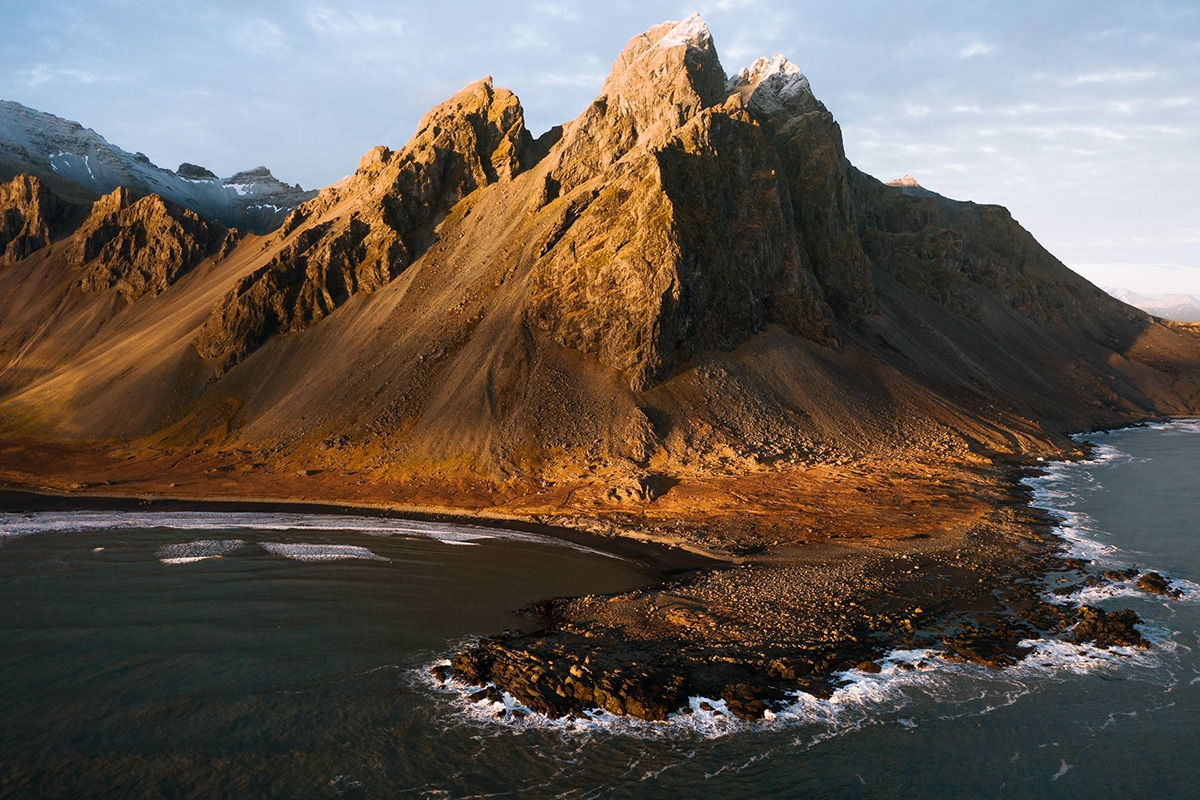 Aerial landscape photography image of the mountains and black sand beach at Stokksnes, Iceland during sunset by Photographer Michael Schauer