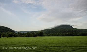 Clouds settling over new-mown meadow