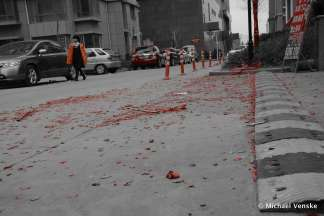 Residential roadway littered with firecracker casings Chinese woman walking into foreground