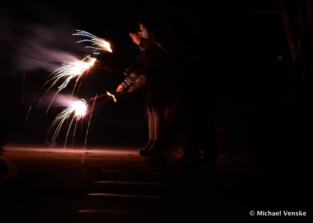 Dark background Chinese woman and young Chinese boy with sparklers