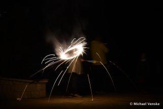 Sparkler light circle illuminating frame with woman behind light circle