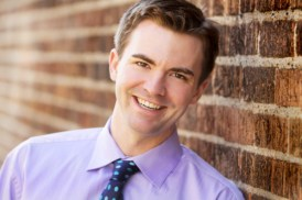 Caucasian male in purple button down shirt with dark blue tie with bright blue polkadots in front of a brick background